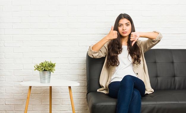 Jeune femme arabe assise sur le canapé, montrant les pouces vers le haut et les pouces vers le bas, difficile de choisir le concept