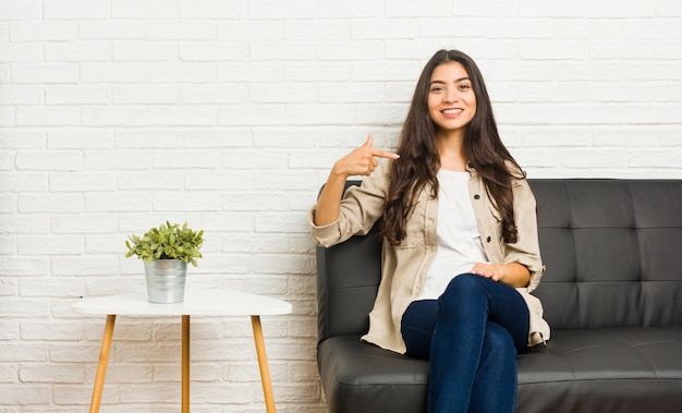Jeune femme arabe assise sur le canapé personne pointant à la main vers un espace copie de chemise, fier et confiant