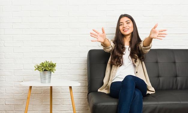 La jeune femme arabe assise sur le canapé se sent confiante en donnant un câlin à la caméra.