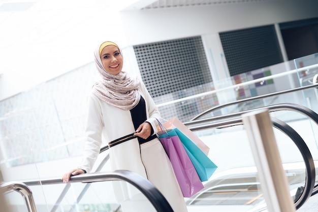 Jeune femme arabe avec des colis debout dans le centre commercial