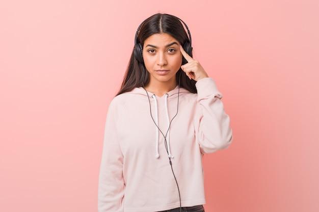Jeune femme arabe écoutant de la musique pointant son temple avec le doigt, pensant, concentré sur une tâche.