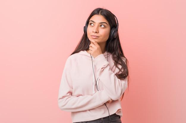 Jeune femme arabe écoutant de la musique en regardant de côté avec une expression douteuse et sceptique.