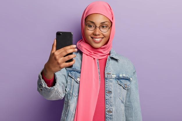 Jeune femme arabe avec une expression joyeuse, porte des lunettes rondes, fait un appel vidéo via cellulaire