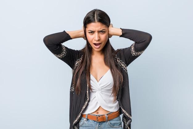 Jeune femme arabe naturelle et jolie couvrant les oreilles avec les mains en essayant de ne pas entendre un son trop fort.