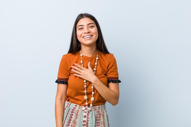 Jeune femme arabe rit à haute voix en gardant la main sur la poitrine.