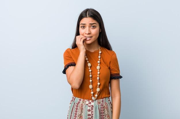 Jeune femme arabe se mordant les ongles, nerveuse et très inquiète.