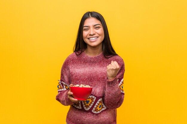 Jeune femme arabe tenant un bol de céréales acclamant insouciant et excité. concept de victoire.