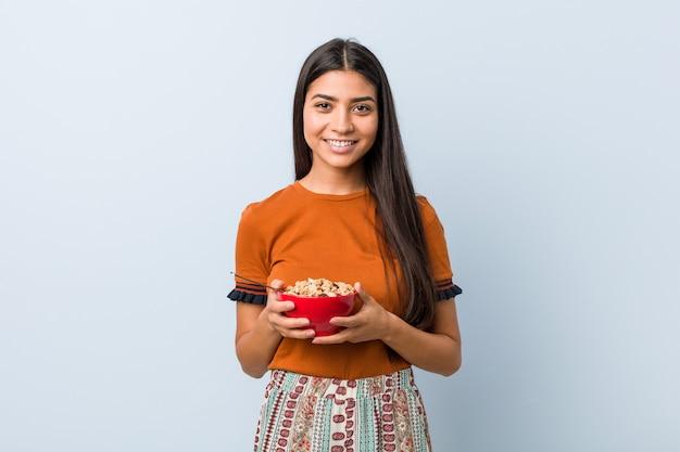 Jeune femme arabe tenant un bol de céréales heureux, souriant et gai.