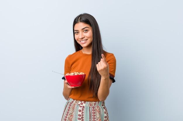 Jeune femme arabe tenant un bol de céréales pointant du doigt vers vous comme si vous vous invitiez à vous rapprocher.