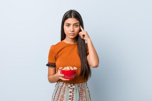 Jeune femme arabe tenant un bol de céréales en pointant sa tempe avec le doigt, pensant, concentrée sur une tâche.