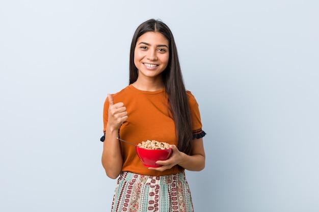 Jeune femme arabe tenant un bol de céréales souriant et levant le pouce vers le haut
