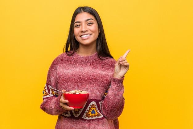 Jeune femme arabe tenant un bol de céréales souriant pointant avec l'index.
