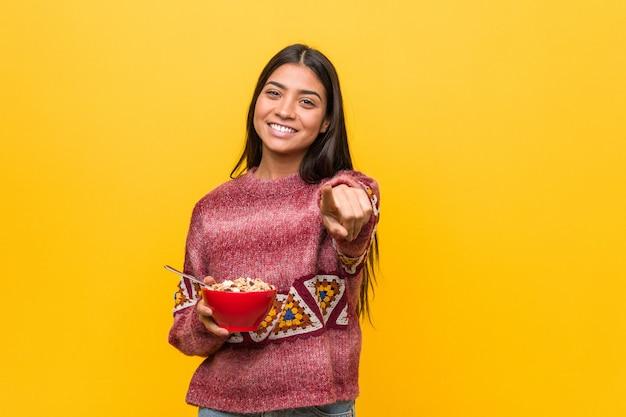 Jeune femme arabe tenant un bol de céréales sourires joyeux pointant vers l'avant.