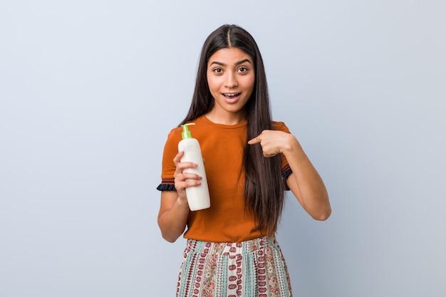Jeune femme arabe tenant une bouteille de crème surprise, pointant le doigt vers lui-même, souriant largement.