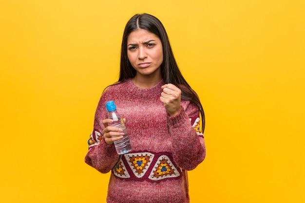 Jeune femme arabe tenant une bouteille d'eau montrant le poing