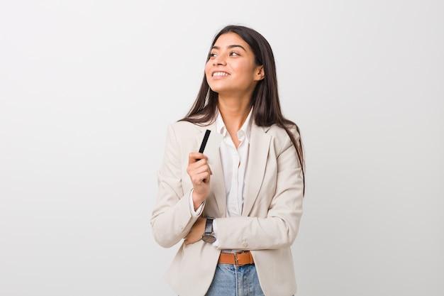 Jeune femme arabe tenant une carte de crédit souriant confiant avec les bras croisés.