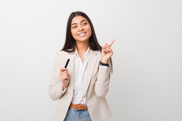 Jeune femme arabe tenant une carte de crédit en souriant joyeusement pointant avec l'index loin.