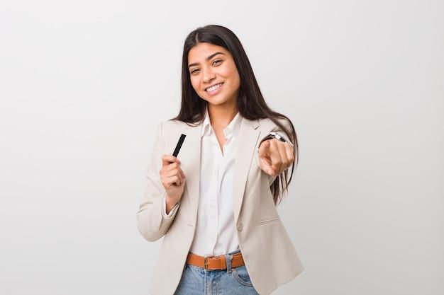 Jeune femme arabe tenant une carte de crédit sourires joyeux pointant vers l'avant.