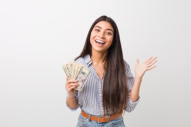 Jeune femme arabe tenant des dollars célébrant une victoire ou un succès