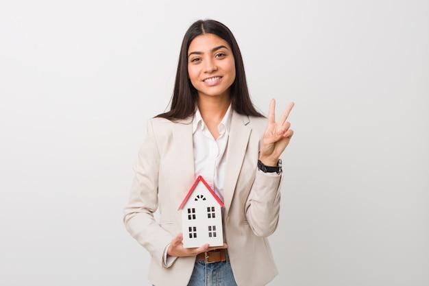 Jeune femme arabe tenant une icône de la maison montrant le numéro deux avec les doigts.