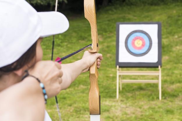 Jeune femme archer tenant son arc visant une cible - concept de sport et de loisirs