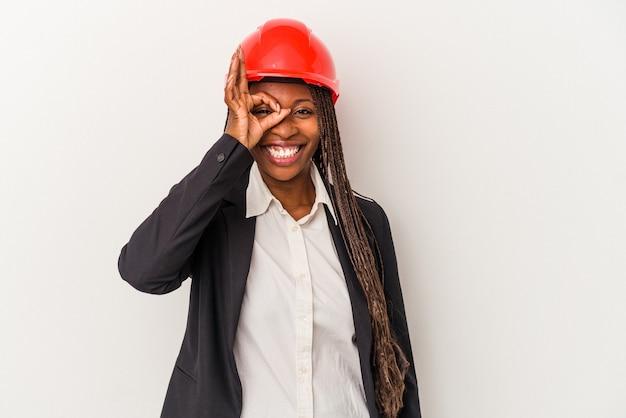 Jeune femme architecte afro-américaine isolée sur fond blanc excitée en gardant un geste ok sur les yeux.
