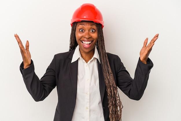 Jeune femme architecte afro-américaine isolée sur fond blanc recevant une agréable surprise, excitée et levant les mains.