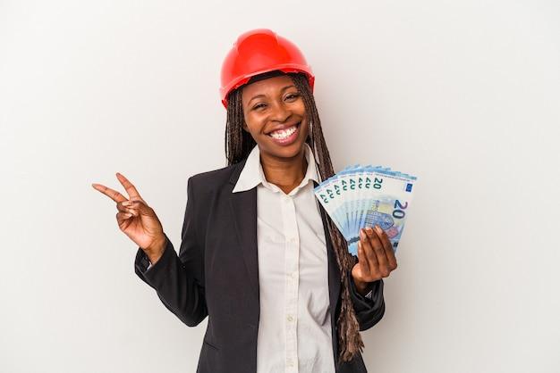 Jeune femme architecte afro-américaine tenant des factures isolées sur fond blanc joyeuse et insouciante montrant un symbole de paix avec les doigts.