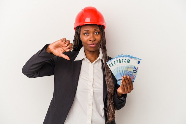 Jeune femme architecte afro-américaine tenant des factures isolées sur fond blanc montrant un geste d'aversion, les pouces vers le bas. notion de désaccord.