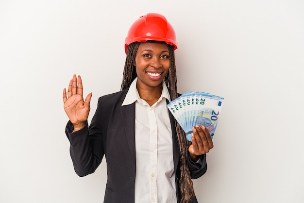 Jeune femme architecte afro-américaine tenant des factures isolées sur fond blanc souriant joyeux montrant le numéro cinq avec les doigts.
