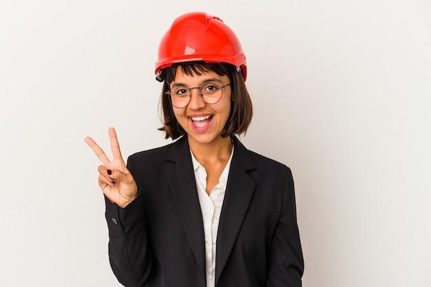 Jeune femme architecte avec casque rouge isolé sur fond blanc joyeux et insouciant montrant un symbole de paix avec les doigts.