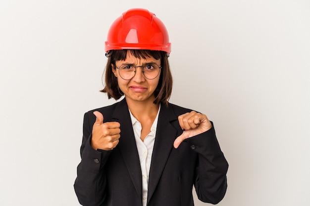 Jeune femme architecte avec casque rouge isolé sur fond blanc montrant les pouces vers le haut et les pouces vers le bas, concept de choix difficile