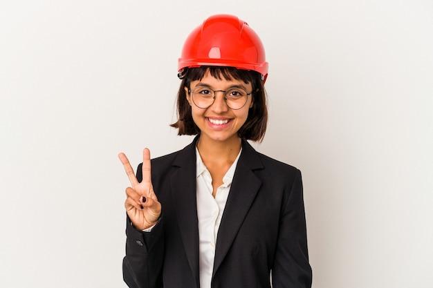 Jeune femme architecte avec casque rouge isolé sur fond blanc montrant le signe de la victoire et souriant largement.