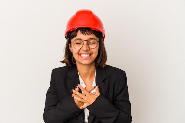 Jeune femme architecte avec casque rouge isolé sur fond blanc rit joyeusement et s'amuse en gardant les mains sur le ventre.