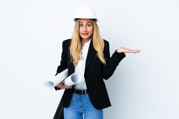 Jeune femme architecte avec casque et tenant des plans sur blanc isolé ayant des doutes avec l'expression du visage confus