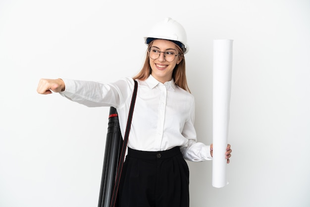 Jeune femme architecte avec casque et tenant des plans isolés sur fond blanc donnant un geste du pouce vers le haut