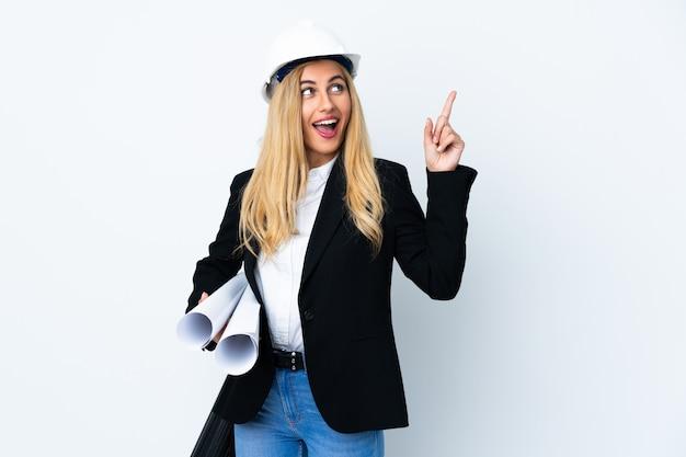 Jeune femme architecte avec casque et tenant des plans sur un mur blanc pointant avec l'index une excellente idée