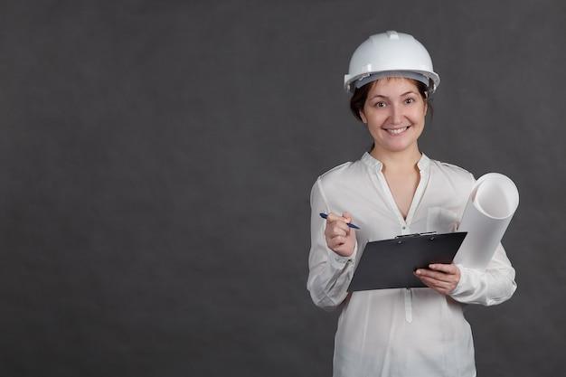 Jeune femme architecte dans un casque de protection prend des notes sur le projet avec un papier dans les mains.