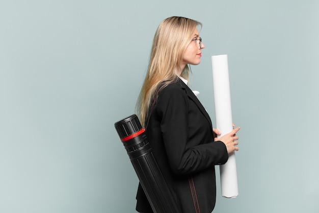 Jeune femme architecte en vue de profil cherchant à copier l'espace devant, à penser, à imaginer ou à rêvasser