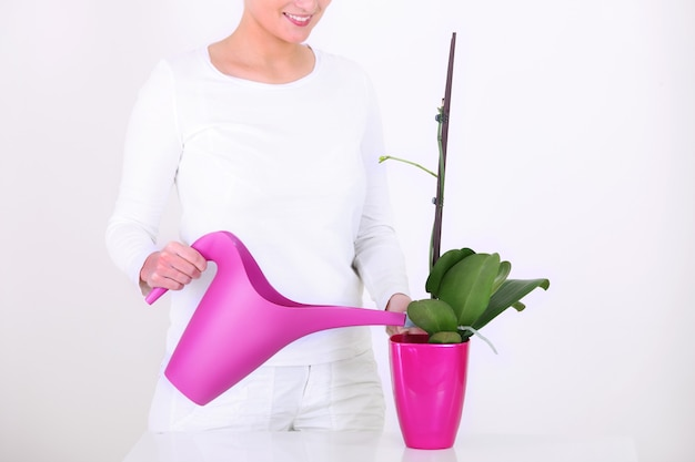 Une jeune femme arrosant une orchidée