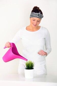 Une jeune femme arrosant une plante