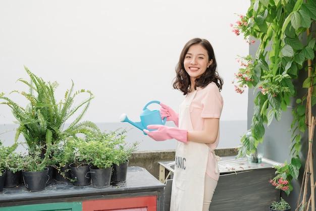 Jeune femme arrosant les plantes dans le jardin de la ferme