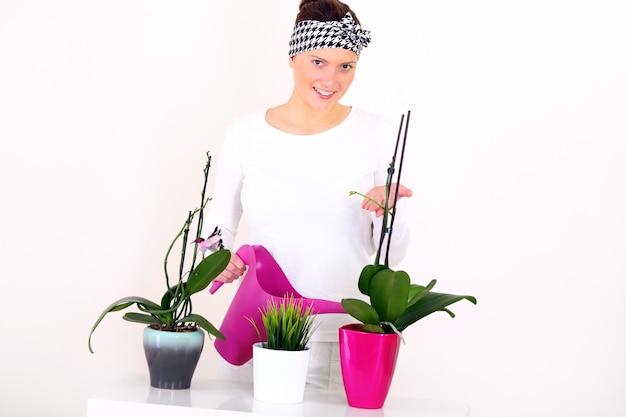 Une jeune femme arrosant des plantes