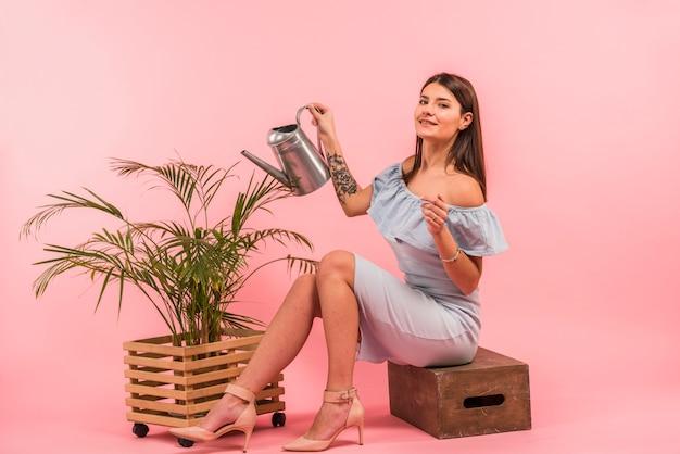 Jeune femme avec arrosoir près de plante d'intérieur