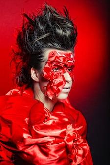 Jeune femme avec art créatif visage rouge