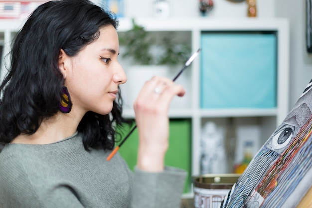 Jeune femme artiste dans son atelier contemplant avec attention son travail tout en le faisant.