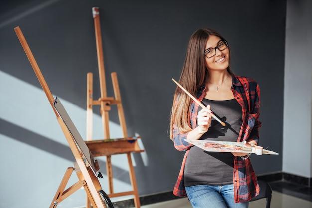 Jeune femme artiste peignant un tableau