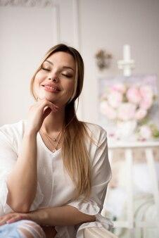 Une jeune femme artiste avec une photo sur un chevalet à la maison. le peintre peint des peintures à l'huile.