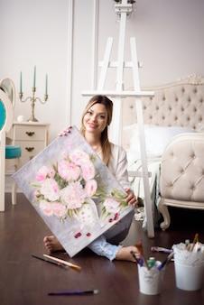Une jeune femme artiste tient une image sur un chevalet à la maison. le peintre peint des peintures à l'huile.