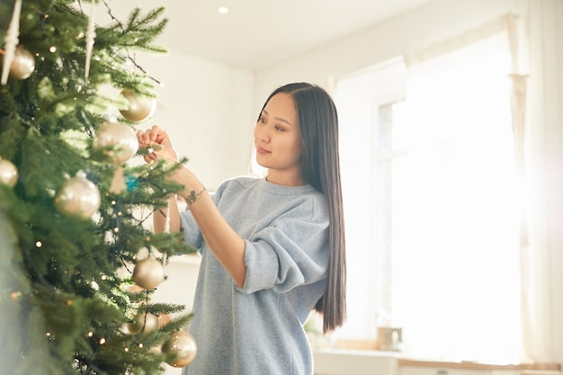 Jeune femme asiatique accrocher des boules de noël sur l'arbre de noël et préparer les vacances
